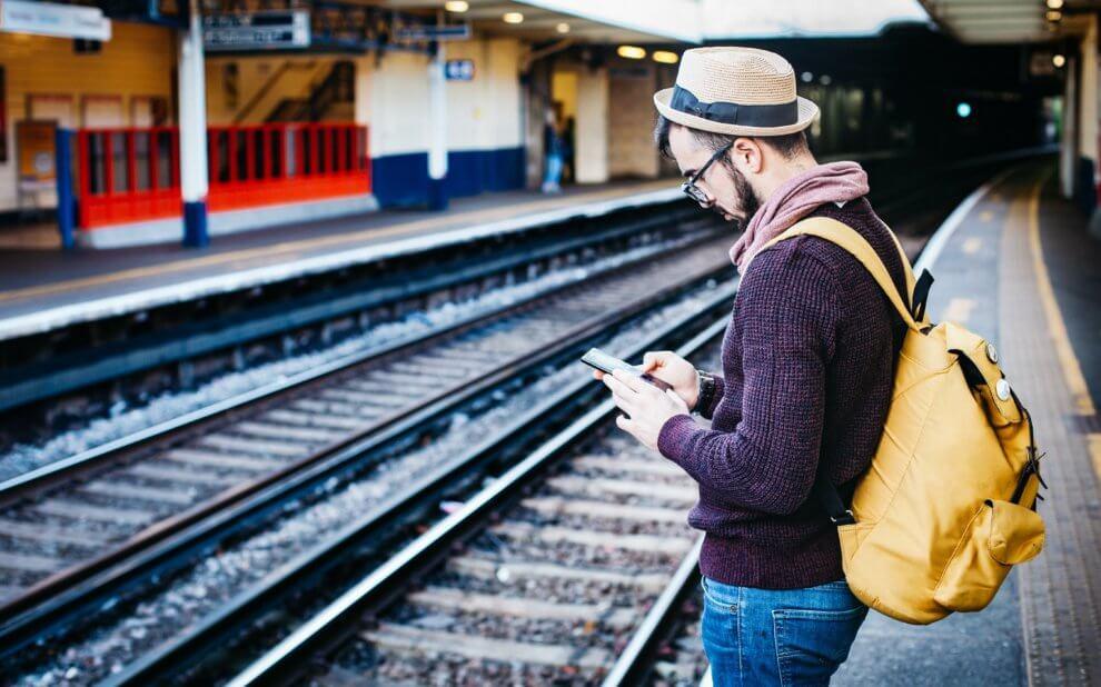 Mann steht auf dem Bahnsteig und schau in sein Handy