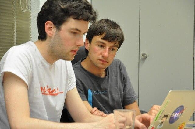 Zwei Männer arbeiten gemeinsam an einem Laptop