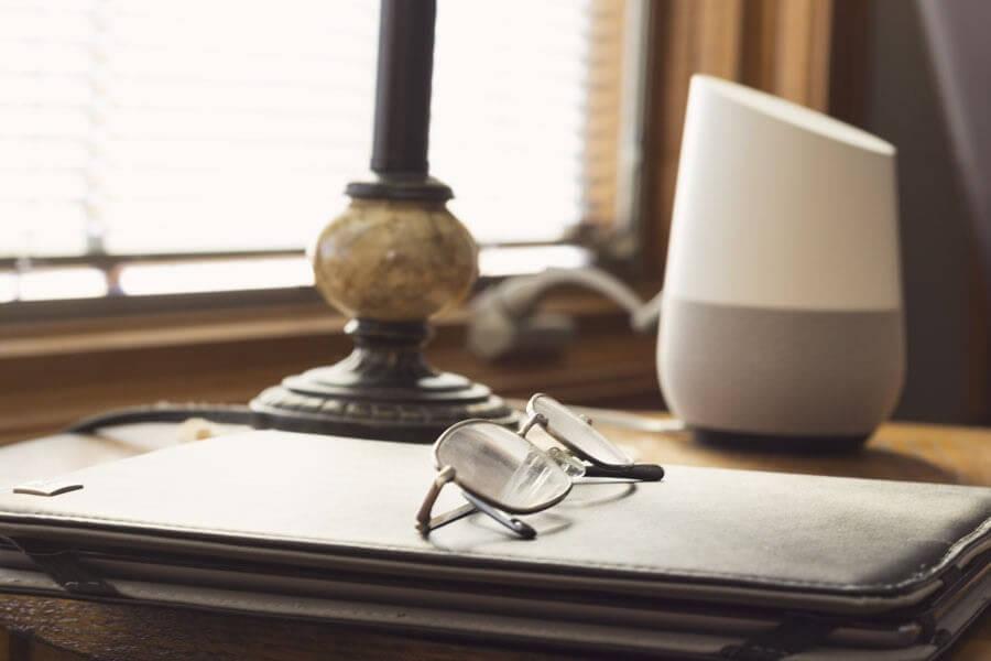 Google Home auf einem Schreibtisch. Im Vordergrund: Eine Schreibmappe mit einer Lesebrille darauf