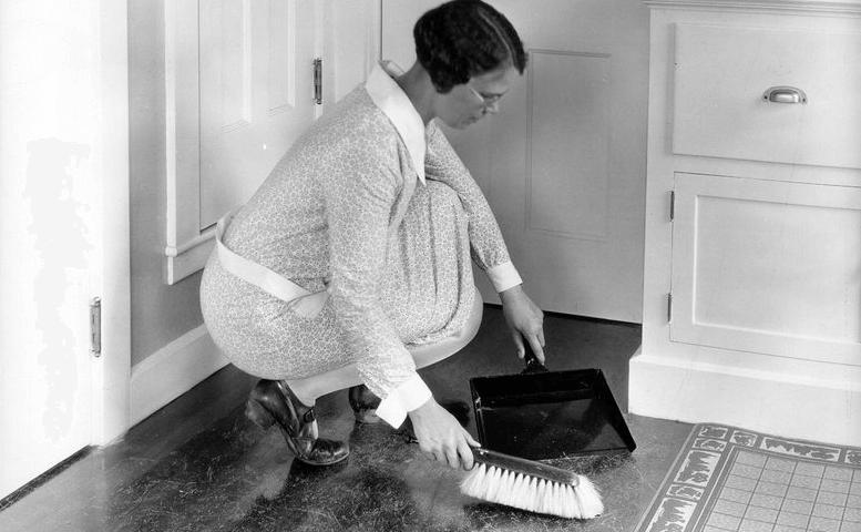 Schwarz/Weiß-Foto: Frau fegt mit Handfeger und Kehrblech den Küchenboden.