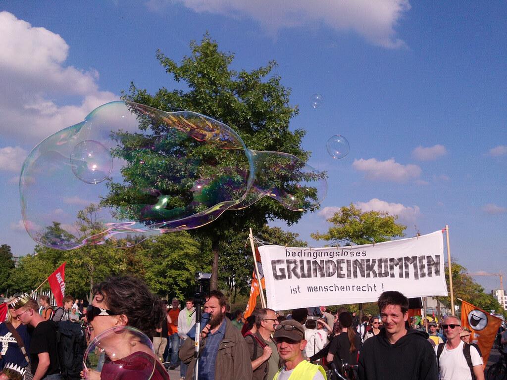 """Transparent auf einer Demo: """"Bedingungsloses Grundeinkommen ist Menschenrecht"""""""