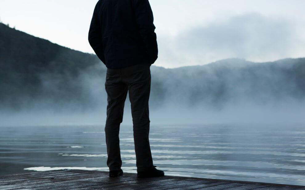 Silhouette einer Person, die auf einen nebligen See schaut