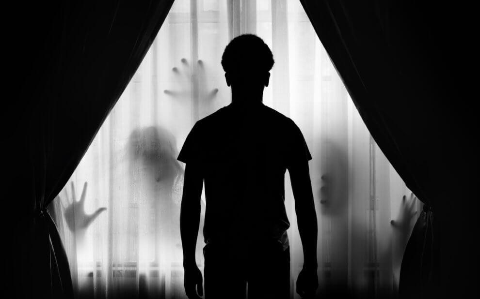 Schattenhafte Hände greifen nach der Silhouette eines Kindes