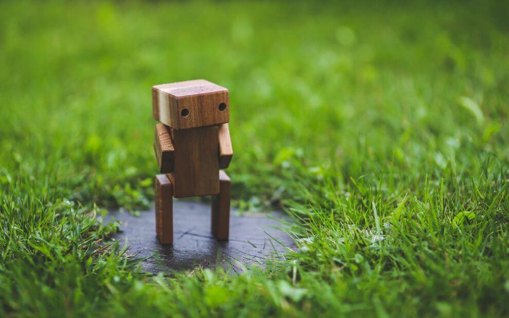 Hölzerne Roboter-Figur auf einem Rasen