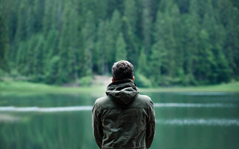 Mann schaut auf einen Waldsee