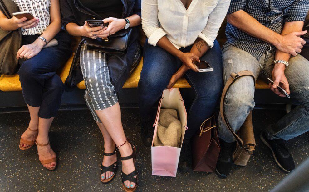 Vier Menschen in der U-Bahn schauen auf ihre Smartphones