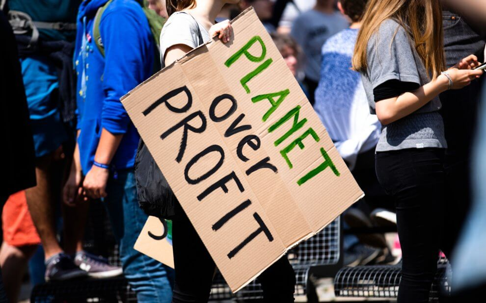 Demonstrant bei Fridays for Future mit dem Schild: Planet over Profit