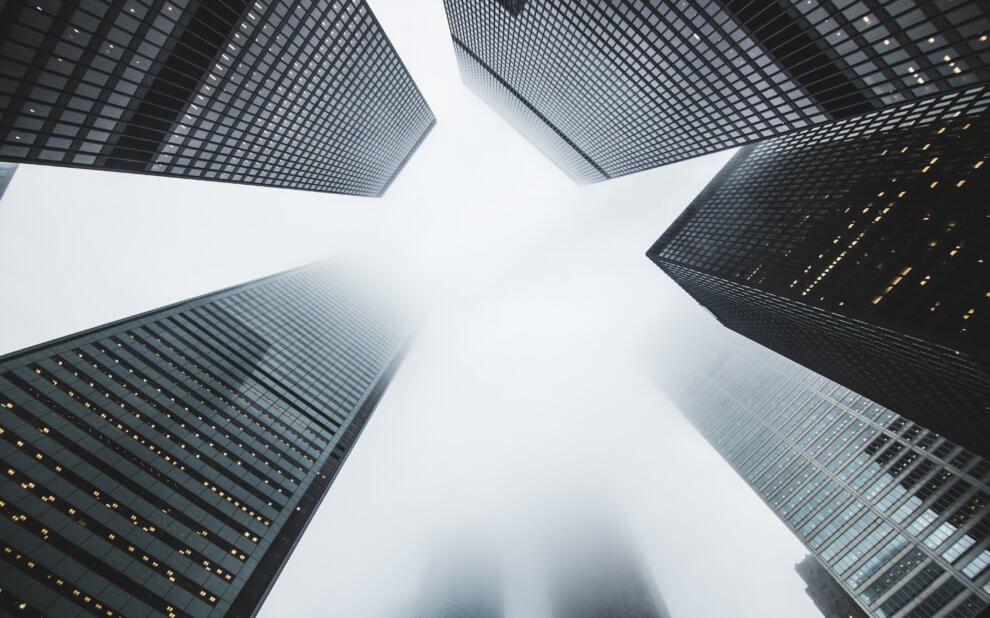 Wolkenkratzer von unten fotografiert. Die Häuserspitzzen verlieren sich im Nebel