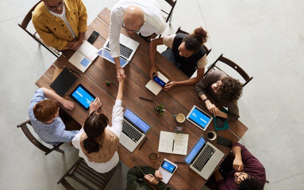 Menschen mit Laptops sitzen gemeinsam am Tisch.