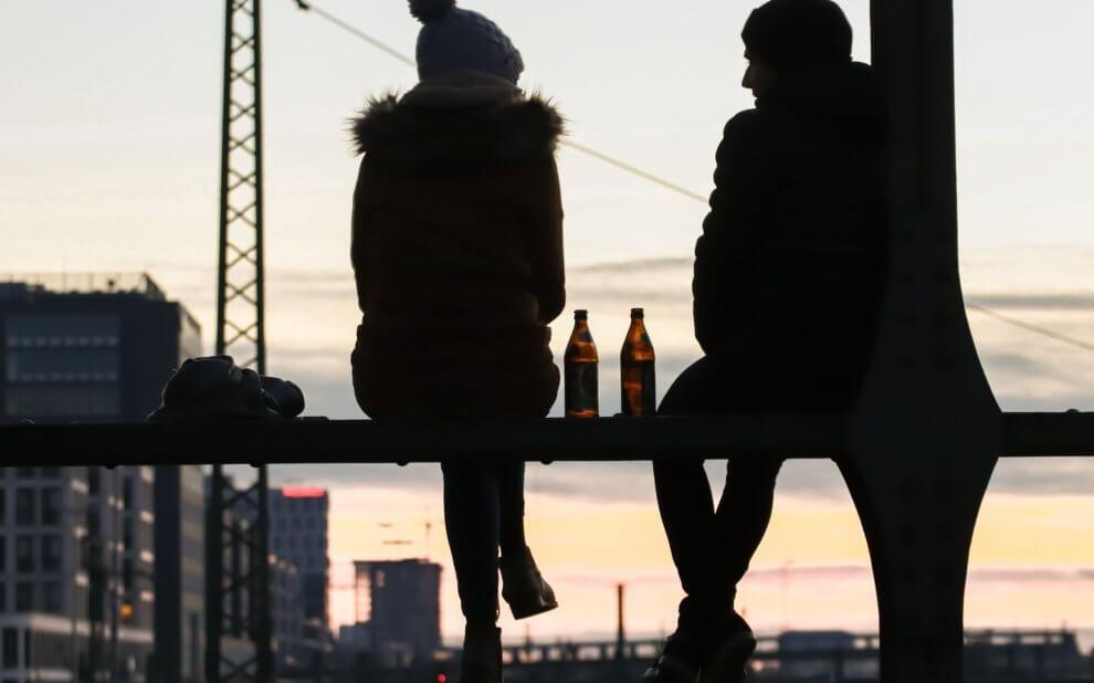 Zwei junge Personen sitzen auf einer Bank, reden und trinken ein Bier.