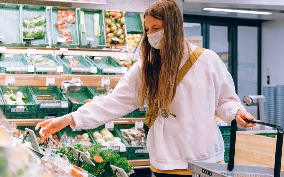 Frau mit Maske kauf Gemüse ein.